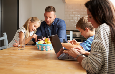 family looking at tablet at kitchen table