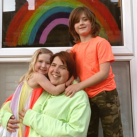 Yasmine and daughter and son in front of their house with a rainbow