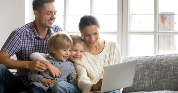 Family of four sitting on sofa smiling at the laptop