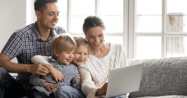 一家四口坐在沙发上对笔记本电脑微笑