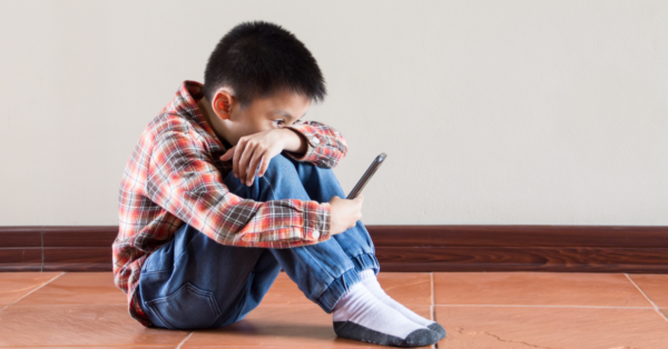 Boy sitting on the floor looking at his smartphone